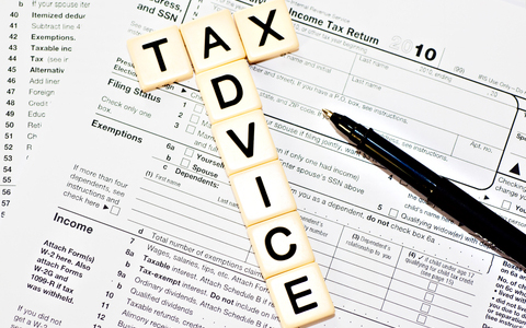 Tax Advice spelled with tiles on top tax document